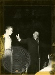 Man standing at microphone by J. R. Cofield