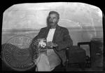 William Faulkner posing with copy of Intruder in the Dust by Phil Mullen