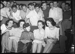 Female students gather around John Louis Roventini, a dwarf, popularly known as Johnny Philip Morris by J. R. Cofield