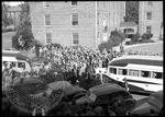 Crowd gathers around buses on campus by J. R. Cofield