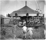 Four children holding hands walk toward a merry go round at a fair by J. R. Cofield