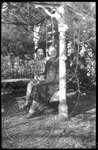 Two women sit on a garden bench by J. R. Cofield