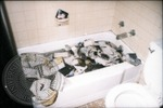 Photographs lie in a bathtub after the Cofield Studio fire by J. R. Cofield