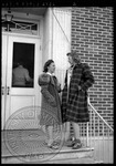 Two female students talk on a buildings steps by J. R. Cofield