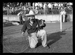 Man in Mexican outfit on the football field with a pig on a chain by J. R. Cofield