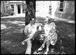 Man and woman talking and sitting on a bench on campus by J. R. Cofield