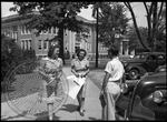 Female students walking to class are greeted my a man by a car by J. R. Cofield