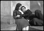 Male and female student cuddle outside a building on campus by J. R. Cofield