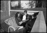 Man and woman talking outside a house on campus by J. R. Cofield