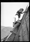 Female student descending a ladder after hanging a banner by J. R. Cofield