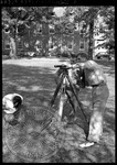 Three men with surveying equipment on campus by J. R. Cofield