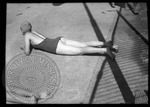 Female sunbathing at a pool laying on her stomach, image 1 by J. R. Cofield