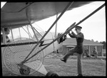 Member of military hand starting a single prop airplane by J. R. Cofield