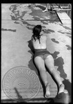 Female sunbathing at a pool laying on her stomach, image 2 by J. R. Cofield