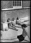 Male and female students sunbathing by J. R. Cofield
