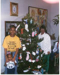 Woman with two kids by Christmas tree by Author Unknown