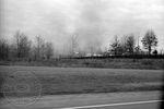 Brush burning off roadway by Edwin E. Meek