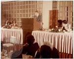 Larry Speakes speaking at podium by Edwin E. Meek