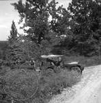 Encamped soldiers pulling open bed wagon with Jeep by Edwin E. Meek