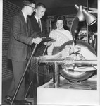 Two men and one woman, unidentified, looking at a machine by Sidna Brower Mitchell