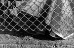 Skirt and Shoes behind Chain Link Fence [Vaught-Hemingway Stadium]. by Amy Evans